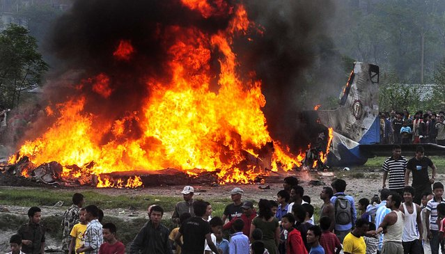 People gather around the burning wreckage of a Sita Air plane near Katmandu, Nepal, on September 28, 2012. The plane carrying trekkers to the Everest region crashed and burned just after takeoff in Nepal's capital, killing the 19 Nepali, British and Chinese people on board, authorities said. (Photo by Associated Press)