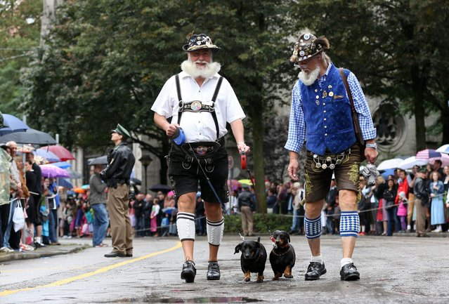 Men wearing traditional Bavarian costumes walk a dog during the traditional Bavarian Oktoberfest festival  in Munich, southern Germany, on September 20, 2014. Germany's world-famous Oktoberfest kicks off with millions of revellers set to soak up the frothy atmosphere in a 16-day extravaganza of lederhosen, oompah music and, of course, beer. (Photo by Christian Charisius/AFP Photo/DPA)