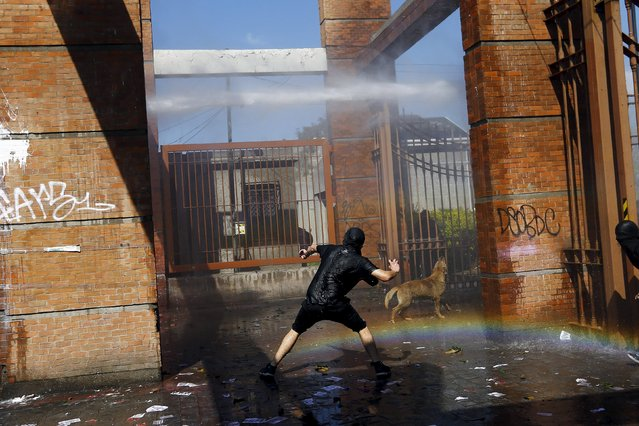 A demonstrator prepares to throw a stone against a riot police vehicle as a rainbow is seen on the ground during a protest marking the country's 1973 military coup, in Santiago, Chile September 13, 2015. (Photo by Ivan Alvarado/Reuters)
