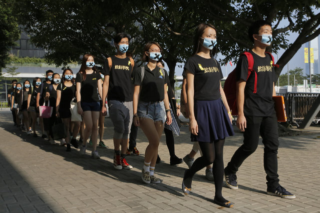 Students of The Hong Kong Academy for Performing Arts wear masks with cross mark during a silence parade near Hong Kong government headquarters in Hong Kong, Tuesday, September 23, 2014. Thousands of Hong Kong college and university students boycotted classes Monday to protest Beijing's decision to restrict voting reforms, the start of a weeklong strike that marks the latest phase in the battle for democracy in the southern Chinese city. (Photo by Vincent Yu/AP Photo)