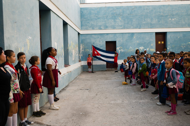 At Manuel Valdes Rodriguez Municipal Primary School in Havana, Cuba, school children shows their patriotism by saluting the flag and singing the national anthem before going to their classrooms in the morning. The anthem was written during the Independence War and says to die for the motherland is to live. (Photo by Sarah L. Voisin/The Washington Post)