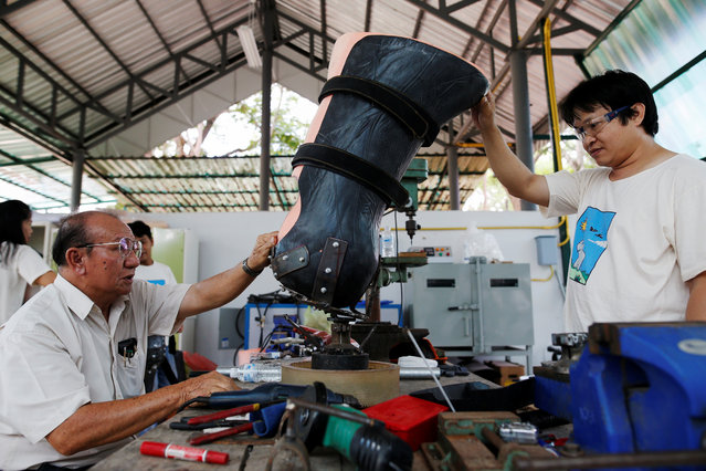 Engineer Boonyu Thippaya (L) and a member of his team adjust a prosthetic leg for an elephant, that was injured by a landmine, at the Friends of the Asian Elephant Foundation in Lampang, Thailand, June 29, 2016. (Photo by Athit Perawongmetha/Reuters)