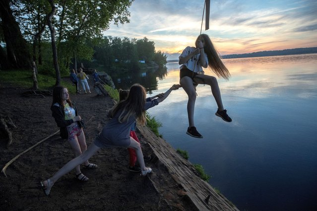 A girl swings on a rope swing over the Volga River in Zavolzhsk, Ivanovo Region, Russia on June 9, 2020. (Photo by Vladimir Smirnov/TASS)