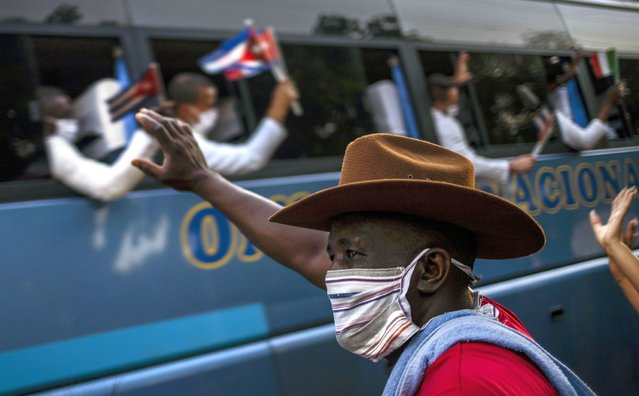 A man waves at the doctors, part the first Cuban medical brigade of the Henry Reeve Contingent, after it arrived in Havana, Cuba, Monday, June 8, 2020. The Cuban doctors had gone to Italy on March 22 to help with the COVID-19 emergency in the Lombardy region. (Photo by Ramon Espinosa/AP Photo)