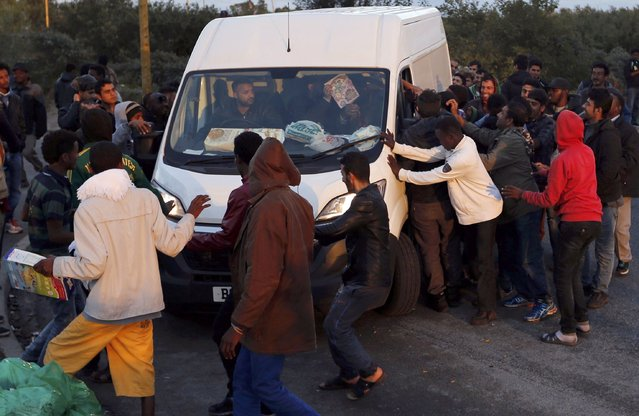 "Migrants surround a truck carrying a refugee aid organisation which arrives to distribute food at the makeshift camp called ""The New Jungle"" in Calais, France, September 18, 2015. (Photo by Regis Duvignau/Reuters)"
