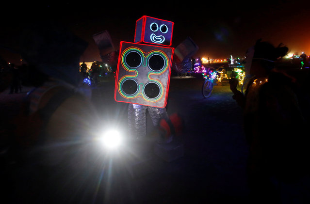 A participant dressed as a robot playing music dances as approximately 70,000 people from all over the world gather for the 30th annual Burning Man arts and music festival in the Black Rock Desert of Nevada, U.S. August 29, 2016. (Photo by Jim Urquhart/Reuters)