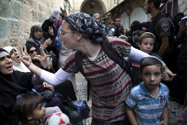 An Israeli woman (C) and a Palestinian woman gesture at one another during a protest by Palestinian women against Jewish visitors to the compound known to Muslims as Noble Sanctuary and to Jews as Temple Mount in Jerusalem's Old City October 14, 2014. The site in Jerusalem's walled Old City has seen repeated disturbances over the years over what Palestinians say are fears of an Israeli threat to the site, which Muslims call the Noble Sanctuary. (Photo by Finbarr O'Reilly/Reuters)
