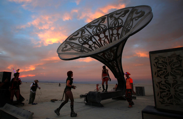 Participants explore the art installation La Victrola as approximately 70,000 people from all over the world gather for the 30th annual Burning Man arts and music festival in the Black Rock Desert of Nevada, U.S. September 1, 2016. (Photo by Jim Urquhart/Reuters)