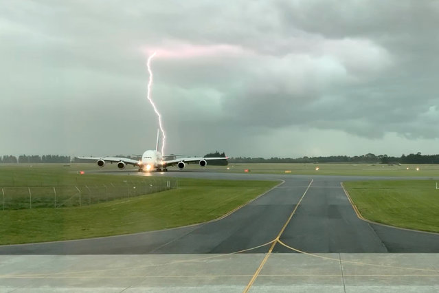 A lightning strikes near an Emirates A380 plane at Christchurch Airport, New Zealand on November 20, 2019 in this still image obtained from a social media video. (Photo by GCH Aviation via Reuters)