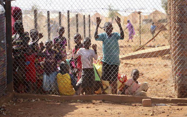 In this February 20, 2018, photo, newly arrived Sudanese refugees wait behind a wire fence at a reception center in Yida, South Sudan. While millions of South Sudanese flee their country in what the United Nations has called the world's fastest-growing refugee crisis since the Rwandan genocide, hundreds of thousands of people from neighboring Sudan have found an unlikely haven there from fighting at home. (Photo by Sam Mednick/AP Photo)
