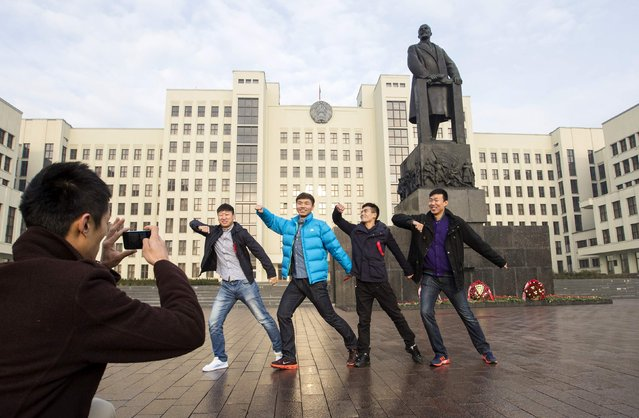 Men pose for a photo at a monument of the Soviet state founder Vladimir Lenin at Independence Square in Minsk November 7, 2014. Several dozen people gathered in Minsk on Saturday to mark Revolution Day, the official public holiday commemorating the 1917 Bolshevik Revolution. (Photo by Vasily Fedosenko/Reuters)