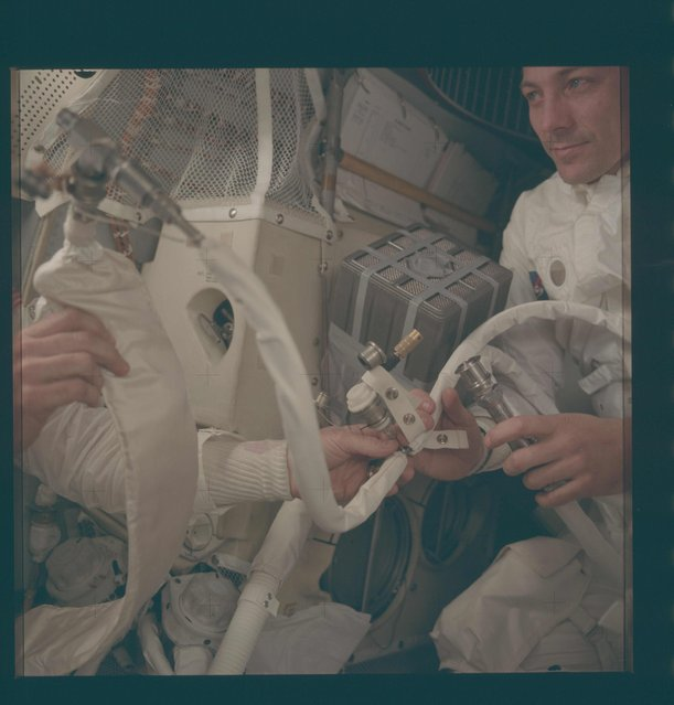 "Astronaut John L. Swigert Jr. (R), command module pilot, and an unidentified astronaut work with some of the temporary hose connections and apparatus which were necessary when the three Apollo astronauts moved from the Command Module to use the Landing Module as a ""lifeboat"" following an explosion during the Apollo 13 mission in this April 1970 NASA handout photo. (Photo by Reuters/NASA)"