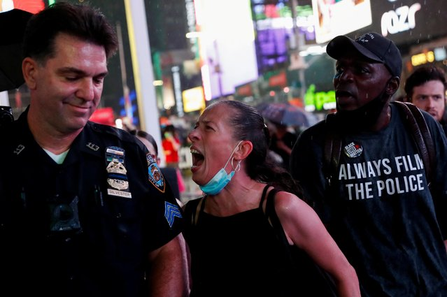 A woman argues with a police officer during a protest following the death of the Black man Daniel Prude, after police put a spit hood over his head during an arrest in Rochester on March 23, at Times Square in New York, U.S. September 3, 2020. (Photo by Shannon Stapleton/Reuters)