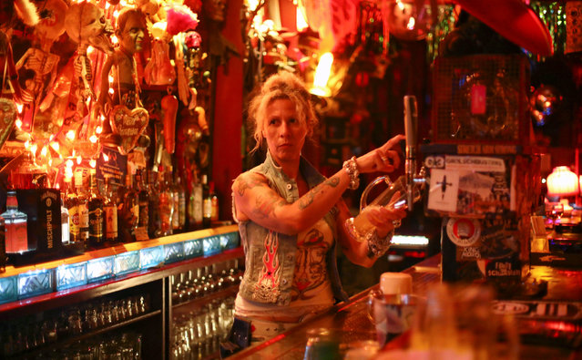 """Lea, owner of the club """"Wild at Heart"""", stands at a bar in Berlin, Germany, September 1, 2016. Lea and her husband Uli, who sings in the band """"Church of Confidence"""", have been running """"Wild at Heart"""" for over 20 years. From swing, salsa and s*x to tango, transvestites and techno, Berlin's nightlife offers something for everyone. Night after night thousands of Berliners and visitors head to hotspots like RAW, an old graffiti-covered train-repair site in the eastern part of the city that was once under Communist rule but is now home to clubs, bars and a pool replete with beer garden. There, in halls and sheds situated along railway lines, people dance to reggae, punk rock, dancehall, hardcore, metal, rap, hip-hop and techno in clubs with names like Cassiopeia and Suicide Circus. (Photo by Hannibal Hanschke/Reuters)"""
