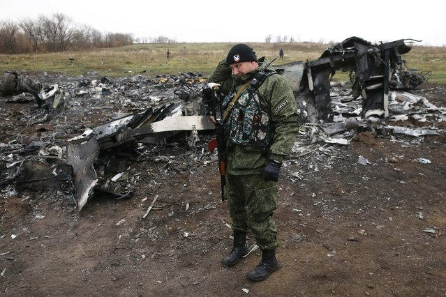 A pro-Russian separatist stands guard in front of debris at the site where the downed Malaysia Airlines flight MH17 crashed, near the village of Hrabove (Grabovo) in Donetsk region, eastern Ukraine November 16, 2014. (Photo by Maxim Zmeyev/Reuters)