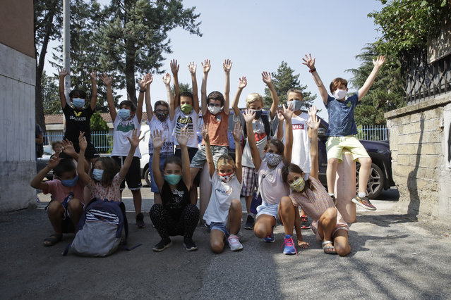 Children of the Mario Lodi primary school pose for group photo wearing masks to protect against COVID-19, at the end of their first day of school, in Rome, Tuesday, September 15, 2020. The reopening of Italian schools marks an important step in a return to pre-lockdown routine after six long months, long after the buzz returned to shopping malls, theaters and beaches, and another test of the government's management of the pandemic. (Photo by Alessandra Tarantino/AP Photo)