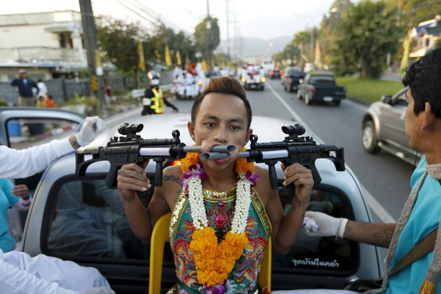A devotee of the Chinese Ban Tha Rue shrine sits on the back of a truck with guns pierced through his cheeks during a procession celebrating the annual vegetarian festival in Phuket, Thailand, October 17, 2015. (Photo by Jorge Silva/Reuters)