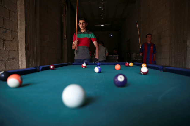 Youth play billiards on the last day of Eid al-Adha celebrations in the rebel held besieged town of Hamouriyeh, eastern Ghouta, near Damascus, Syria September 15, 2016. (Photo by Bassam Khabieh/Reuters)