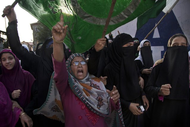 Kashmiri Muslim women hold an Islamic flag and shout pro-freedom slogans during a protest in Srinagar, Indian controlled Kashmir, Tuesday, September 27, 2016. Kashmir is witnessing the largest protests against Indian rule in recent years, sparked by the July 8 killing of a popular rebel commander by Indian soldiers. The protests, and a sweeping security crackdown, have all but paralyzed life in Indian-controlled Kashmir. (Photo by Dar Yasin/AP Photo)