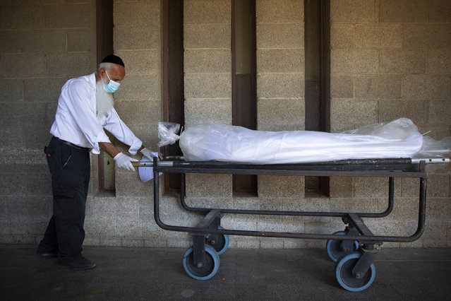 """A worker from """"Hevra Kadisha"""", Israel's official Jewish burial society, caries a body before a funeral procession at a special morgue for COVID-19 victims, during a nationwide lockdown to curb the spread of the coronavirus, in the central Israeli city of Holon, near Tel Aviv, Monday, October 12, 2020. (Photo by Oded Balilty/AP Photo)"""