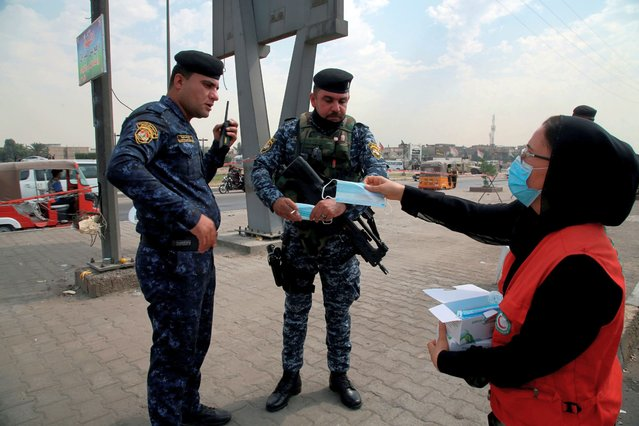 A health worker distributes face masks to security forces as a precaution against the coronavirus while Shiite pilgrims march to Karbala for the Arbaeen ritual in Baghdad, Iraq, Sunday, October 4, 2020. The holiday marks the end of the forty day mourning period after the anniversary of the martyrdom of Imam Hussein, the Prophet Muhammad's grandson in the 7th century. (Photo by Khalid Mohammed/AP Photo)