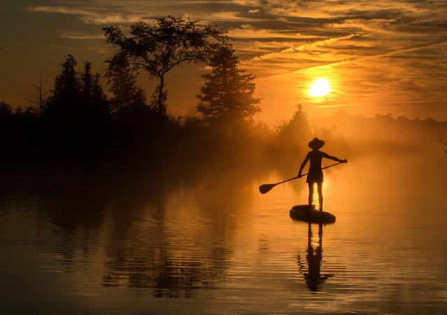 Early morning paddle boarder enjoys late days of summer on Trent Severn Waterway in Rosedale, Ont., Thursday, September 3, 2020. (Photo by Canadian Press/Rex Features/Shutterstock)