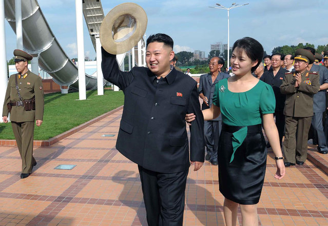 In this July 25, 2012 file photo released by the Korean Central News Agency (KCNA) and distributed in Tokyo by the Korea News Service, North Korean leader Kim Jong Un, accompanied by his wife Ri Sol Ju, waves to the crowd as they inspect the Rungna People's Pleasure Ground in Pyongyang. (Photo by AP Photo/Korean Central News Agency via Korea News Service)