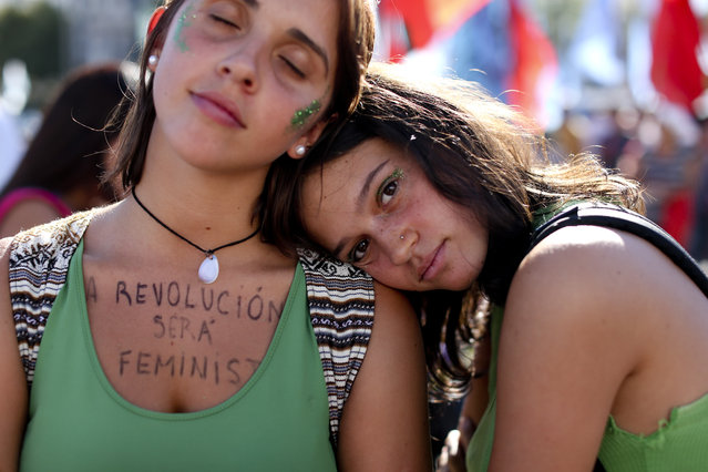 """A woman wears a message on her chest that reads in Spanish: """"The revolution is feminist"""" during a demonstration celebrating International Women's Day, in Buenos Aires, Argentina, Thursday, March 8, 2018. Tens of thousands of people gathered in Argentina's capital to condemn violence against women while commemorating International Women's Day. (Photo by Natacha Pisarenko/AP Photo)"""