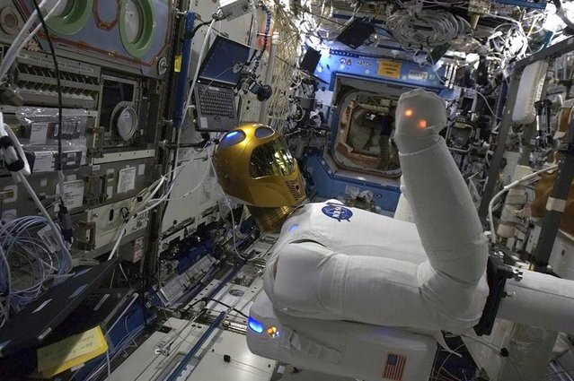 """NASA's Robonaut 2, the first humanoid robot in space, is put through its paces aboard the International Space Station, as seen in a photo sent by Canadian astronaut Chris Hadfield on March 18, 2013. Robonaut was designed with the intention of eventually taking over tasks deemed too dangerous or mundane for astronauts. """"It will be even more interesting when his legs are installed"""", Hadfield said. (Photo by Chris Hadfield/CSA via Reuters)"""