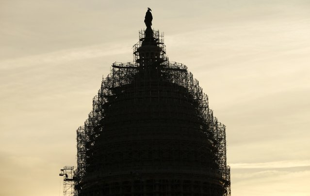 A worker (L) reaches for supplies while working atop the scaffolded dome of the U.S. Capitol in Washington December 4,  2014. The Capitol Dome is undergoing a multi-year restoration to stop the current level of deterioration in the Dome's cast iron as well as ensuring the protection of the interior of the Dome and Rotunda. The restoration project includes removal of old paint, repairs to the cast iron and stone, and repainting. (Photo by Kevin Lamarque/Reuters)