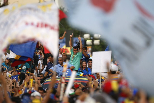 Venezuela's opposition leader and presidential candidate Henrique Capriles (C) greets supporters during a campaign rally in the state of Zulia April 10, 2013. Venezuelans will hold presidential elections on April 14. (Photo by Isaac Urrutia/Reuters)