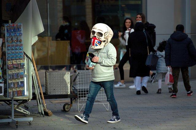 A street vendor wearing a skull mask in Birmingham on November 2, 2020, ahead of a national lockdown for England from Thursday. (Photo by Jacob King/PA Images via Getty Images)
