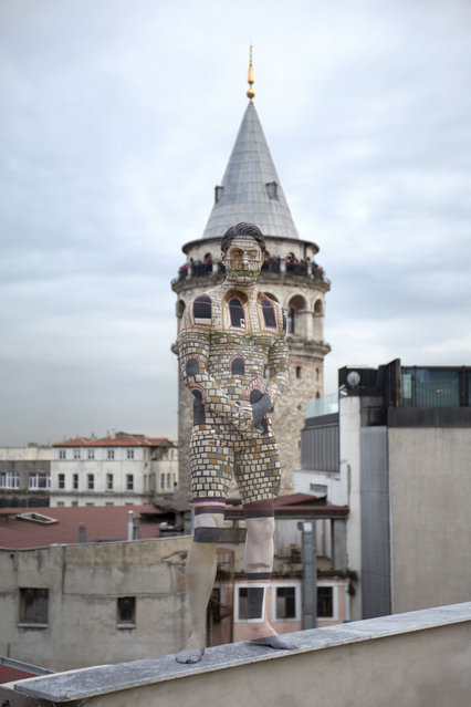 A man blends into Istanbuls famous Galata Towar in Turkey. (Photo by Trina Merry/Caters News)