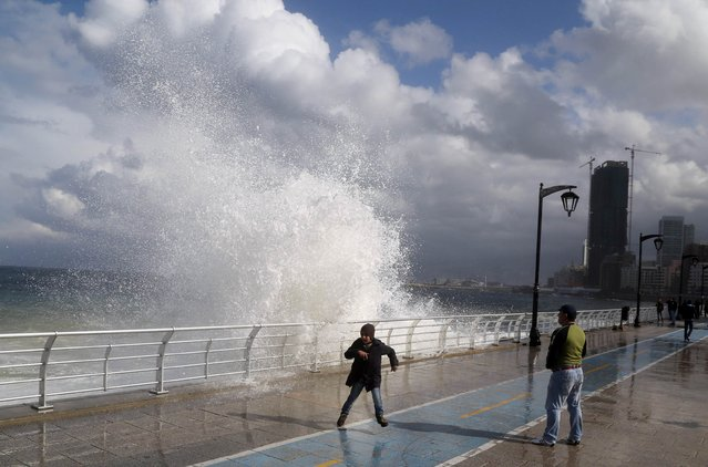 A boy plays in front of a wave crashing into Beirut's Corniche, a seaside promenade, as high winds sweep through Lebanon during a storm, November 26, 2014. (Photo by Aziz Taher/Reuters)