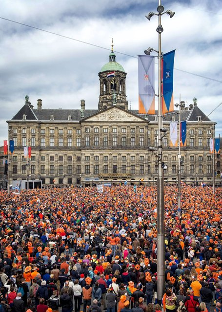 Peope, most of them wearing orange tee shirts, hats or plastic crowns, gather on April 30, 2013 at the Dam Square in Amsterdam, The Netherlands, to attend the investiture of the country's new King. Dutch Crown Prince Willem-Alexander became Europe's youngest monarch on Tuesday after his mother, Queen Beatrix, abdicated and his country hailed the avowedly 21st-century king with a massive, orange-hued party. (Photo by Koen van Weel/AFP Photo)