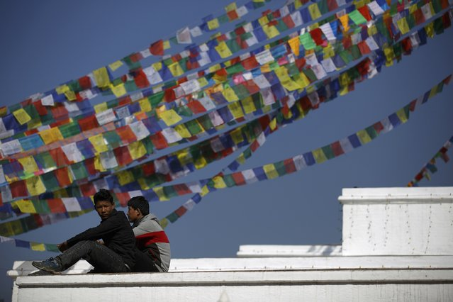 Men sit in front of the prayer flags at the premises of Boudhanath Stupa in Kathmandu December 23, 2014. (Photo by Navesh Chitrakar/Reuters)