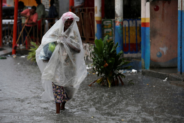 A woman protects herself from rain after Hurricane Matthew in Les Cayes, Haiti, October 17, 2016. (Photo by Andres Martinez Casares/Reuters)