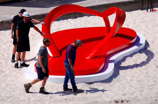 """Workers install a sculpture that is part of the annual outdoor exhibition known as """"Sculpture by the Sea"""" at Tamarama Beach in Sydney, Australia October 19, 2016 which showcases sculptures by local and international artists along the coastline between Bondi and Tamarama beaches. (Photo by David Gray/Reuters)"""