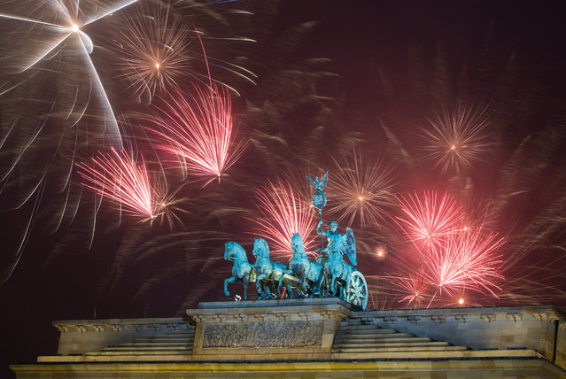 Fireworks explode during the New Year's party at Brandenburg Gate in Berlin, Thursday, January 1, 2015. (Photo by Lukas Schulze/AP Photo/DPA)