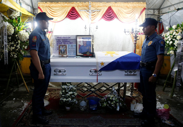 Policemen stand guard in front of the flag-draped coffin of fellow police officer Rancel Cruz, who police investigators said was shot dead by a drug addict, in Manila, Philippines October 19, 2016. (Photo by Erik De Castro/Reuters)