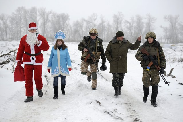 Local residents dressed as Father Frost, an equivalent of Santa Claus, and his granddaughter Snegurochka (Snow-Maiden), walk with servicemen as they visit check points of the Ukrainian army and self-defence units to congratulate the military with the coming of a New Year, near Lysychansk, Luhansk region, January 2, 2015. (Photo by Maksim Levin/Reuters)