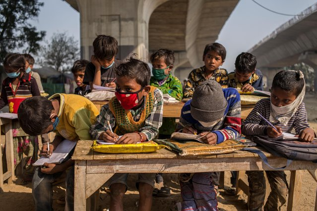 Underprivileged children sit at desks underneath a flyover at an improvised classroom set up at a construction site on December 09, 2020 in New Delhi, India. Many underprivileged children are unable to afford the laptops or tablet computers needed for online classes, leaving them without access to education as the Covid-19 pandemic rages across India. The improvised school, set up by graduate students who are still looking for work, is located at a construction site underneath a metro railway track in the dusty streets of the country's capital. The pandemic is hit the underprivileged members of society the hardest, forcing millions of people out of work, out of homes, and back into destitution, as the country quickly approaches a tally of 10 million infections. (Photo by Anindito Mukherjee/Getty Images)