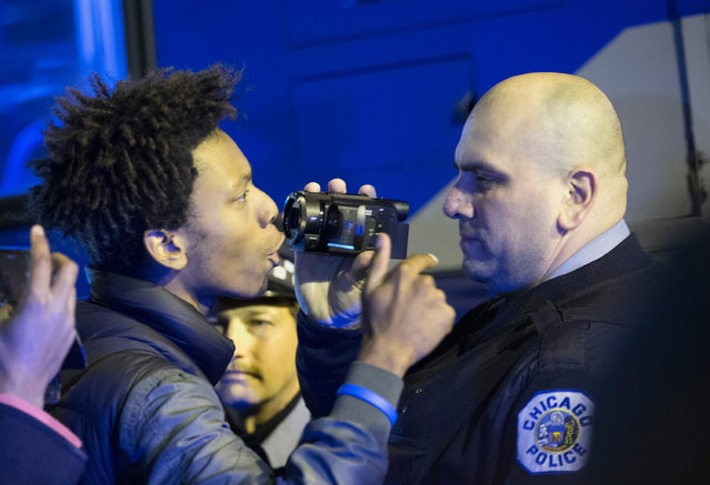 Demonstrators confront police during a protest following the release of a video showing Chicago Police officer Jason Van Dyke shooting and killing Laquan McDonald on November 24, 2015 in Chicago, Illinois. Van Dyke was charged today with first degree murder for the October 20, 2014 shooting in which McDonald was hit with 16 bullets. (Photo by Scott Olson/Getty Images)
