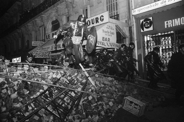 """CRS riot policeman wielding shields and batons cross a barricade to charge striking students near the Sorbonne, Paris, France, May 10, 1968. """"At first I did not understand what was going on. For hours on the first day of rioting the police allowed the students to do as they liked. The students wrecked everything, ripped up paving stones, chopped down trees, erected barricades, set cars on fire. Later, in a matter of minutes, the CRS charged the students. I asked myself """"Why hadn't they charged earlier?"""". I soon understood why. The authorities wanted the public to see the devastation"""". (Photo by Gökşin Sipahioğlu/SIPA Press)"""