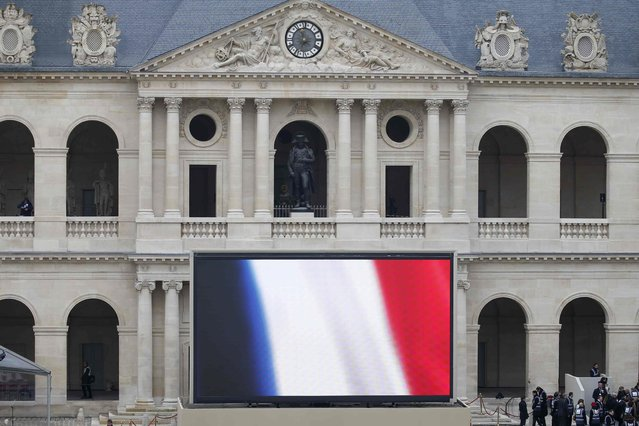 A French flag appears on a big screen at the bottom of the statue of French Emperor Napoleon at the Hotel des Invalides in Paris, France, after a ceremony to pay a national homage to the victims of the Paris attacks, November 27, 2015. (Photo by Charles Platiau/Reuters)