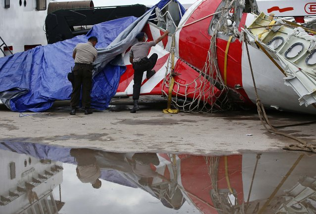 Indonesian police remove tarpaulin from part of the tail of the AirAsia QZ8501 passenger plane in Kumai Port, near Pangkalan Bun, Central Kalimantan January 12, 2015. Flight QZ8501 vanished from radar screens over the northern Java Sea on December 28, 2014 less than half-way into a two-hour flight from Indonesia's second-biggest city of Surabaya to Singapore. (Photo by Darren Whiteside/Reuters)