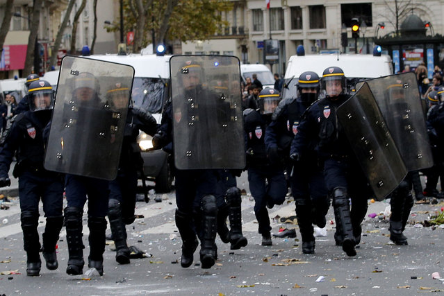 Policemen run toward activists during a protest ahead of the 2015 Paris Climate Conference, in Paris, Sunday, November 29, 2015. More than 140 world leaders are gathering around Paris for high-stakes climate talks that start Monday, and activists are holding marches and protests around the world to urge them to reach a strong agreement to slow global warming. (Photo by Christophe Ena/AP Photo)