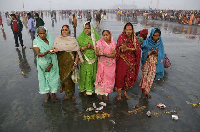 Hindu pilgrims offer prayers to the Sun God after taking holy dips to mark Makar Sankranti festival in Gangasagar, India, Thursday, January 15, 2015. The annual holy dip, that devotees believe absolves them of sin, was held Jan. 14-15 at the confluence of the Bay of Bengal and Ganges River. (Photo by Bikas Das/AP Photo)