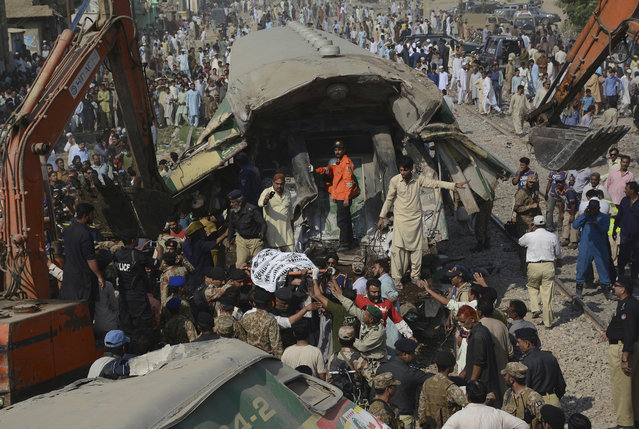 Volunteers carry an injured passenger from the wreckage of a train that collided with another train in Karachi, Pakistan, Thursday, November 3, 2016. Pakistani officials say a train crash has killed more than a dozen people in the southern port city. (Photo by Shakil Adil/AP Photo)