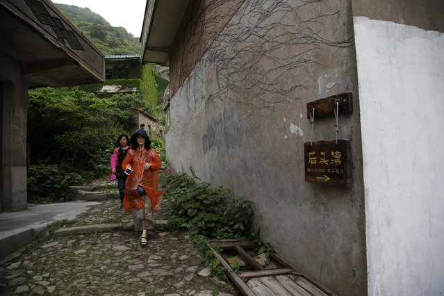 """In this May 19, 2018, photo, tourists pass by a sign which reads """"Houtouwan"""" leading to the former fishing village of Houtouwan on the remote island of Shengshan, 90 kilometers off the coast of Shanghai. Only 5 of the 3,000 residents remain in what some call a """"ghost village"""" that draws visitors down perilous footpaths winding past structures worn down by roots, rain, vines and wind. (Photo by Sam McNeil/AP Photo)"""